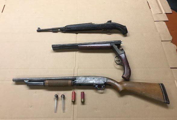Two shotguns with ammunition and a rifle located in the residence.